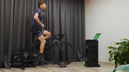 estacionário : Male doing cycling training on home bicycle smart trainer. Confident man in cycle apparel doing workouts on bike at home, sweating and unzipping jersey. Young boy pedaling on cycle to lose weight