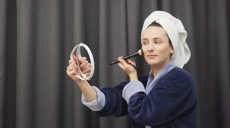 limpar : Beautiful woman applying cosmetics on face. Young happy female in blue bathrobe anf towel on head putting blush on face. Smiling charming woman preparing to be ready in the morning. Health and beauty