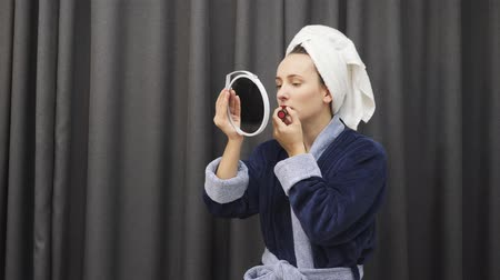 косметический : Woman painting lips with red lipstick. Girl doing bright makeup. Female in bathrobe applying lipstick. Beautiful makeup. Health and beauty Стоковые видеозаписи