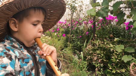 ón : Baby boy in straw hat trying to play on wooden music instrument in green garden. Little cute boy enjoying to play on flute, close up side view