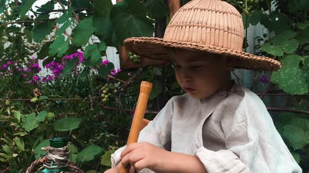 笛 : Close up side view of happy funny cute little boy in straw hat trying and learning to play on wooden flute, close up view