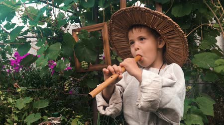 ón : Portrait of happy funny little boy diligently trying to play on tin wistle. Cute charming baby boy playing on flute