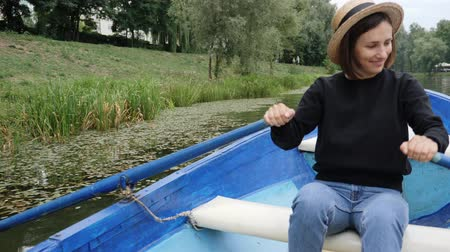 rowboat : Young happy girl in retro hat floating on blue wooden boat on lake with water lilies. Shy girl rowing oars on lake in city park. Smiling young girl sailing on wooden boat along city park