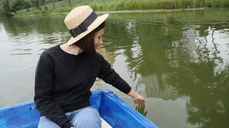 rowboat : Woman in straw hat holds her hand on water. Happy girl resting on boat on lake. Woman smiling at camera. Girl leads palm on water. Woman hand gently touches the surface of water in lake