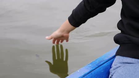 rowboat : Young girl gently touching water on lake. Woman leads palm on green water. Close up of woman hand touches water in park. Woman hand touching water on lake.