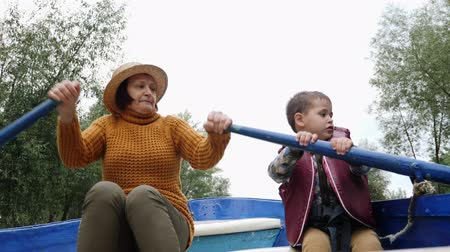 remo : Grandmother floating on blue wooden boat with grandchild on lake in park. Happy family on boat in park. Granny and grandson talking and sitting on wooden boat on lake in city park Filmati Stock