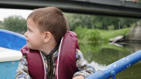 kürek çekme : Portrait of adorable little child laughing and smiling on lake. Happy little boy sitting in boat and paddling. Close up view of happy smiling boy on lake in park. Little cute child holding paddle