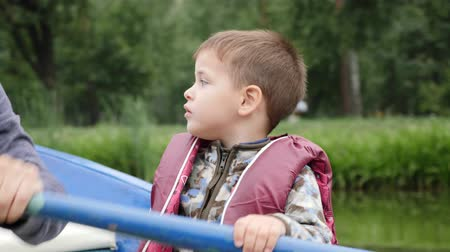 rowboat : Portrait of little adorable child spending time in park on lake. Happy little boy sitting in boat and looking around. Close up view. Cute little child in life jacket sits in wooden boat. Stock Footage