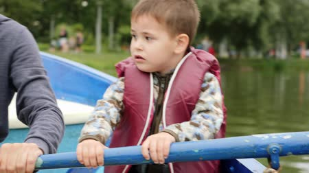 rowboat : Adorable little boy in life jacket rows fast on lake. Close up view of little cute child sitting in boat. Funny child paddling in wooden boat on lake in park. Little boy having fun in park with lake Stock Footage