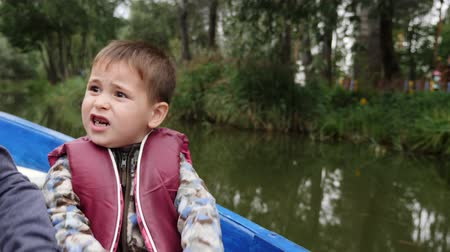 rowboat : Portrait of little adorable child holds paddle. Close up view of little cute boy smiling at camera on lake. Happy child holds paddle and talking at camera in park.