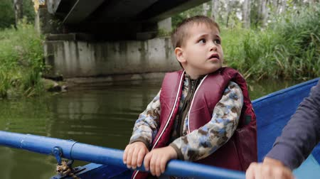 rowboat : Little happy boy holds oar sitting in boat in city park. Little child sits in blue boat and floats under pedestrian bridge. Portrait of cute child rowing on wooden boat along green sedge on lake