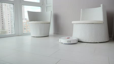 ev işi : Robot vacuum cleaner tidy up on the balcony. Robot cleaner cleaning the tile flooring in the room Stok Video