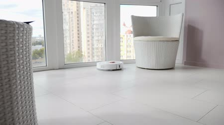 zametání : White robotic vacuum cleaner is vacuuming dirty tile floor at modern room. Smart home. Modern cleaning technology