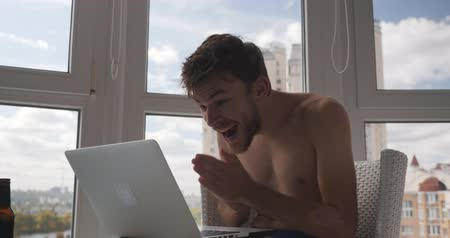 üstsüz : Young caucasian male trader in underpants, sitting at balcony with laptop, won deal in the financial market, cheerful, happy and joyful. Happy man won online video game on computer Stok Video