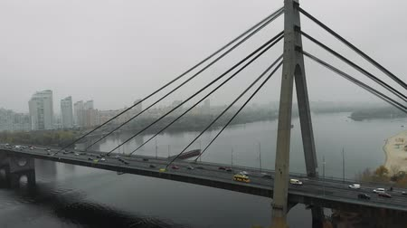 комбинированный : Huge concrete gray bridge with steel cables is combined two sides of metropolis in industrial smog. Cars and public transports with heavy traffic are riding through river on bridge, aerial top view