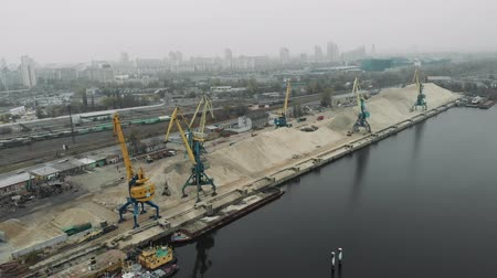 marine technology : Industrial part of the city with cargo construction cranes and old cargo railway tracks. Extraction of sand from barge to pile of sand with cargo trucks