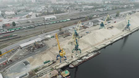 marine technology : Sand Iron industrial barge with sand floating near cargo working cranes. Extraction of river sand in docks