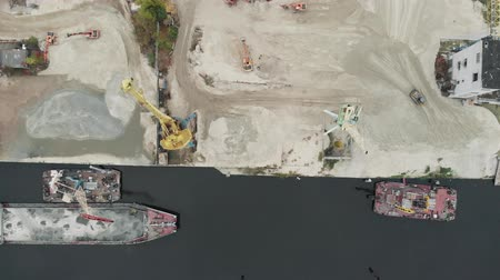 goederentrein : Port cranes on the river bank produce sand. Port cranes with a bucket on the river bank. Sand extraction with trucks and excavators Stockvideo