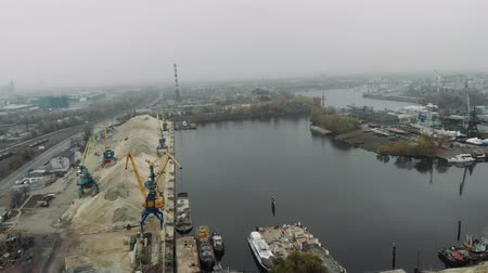 goederentrein : Aerial view of industrial gray city covered in fog and smog. Cargo trains and railway station near river docks and cargo port cranes Stockvideo