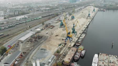 sand bank : Aerial view of port working cranes extracting sand from iron barge and scow on river bank in industrial dirty city in smog