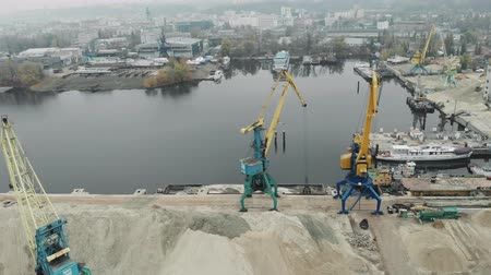 goederentrein : Aerial view of industrial city and cargo working cranes in docks extracting river sand from iron barge