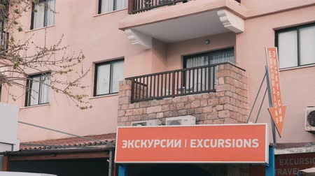 здесь : Billboard with excursion word. Poster on front of the building. House with advertisement. Placard of excursions. Tourist excursions