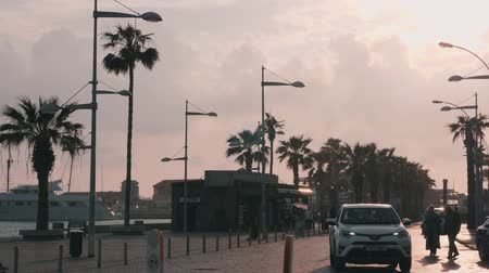 keresztül : March, 16, 2019  Cyprus, Paphos quay with marina at rainy weather. Seacoast promenade with tourists and cars. People walking across tourist area in Paphos. Slow motion