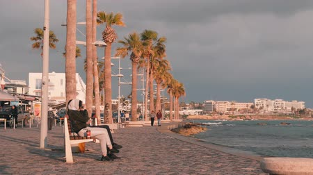 area of port : March, 16, 2019  Cyprus, Paphos Tourist promenade in Paphos, Cyprus. People walking on quay. Pedestrian path with relaxing people on seacoast. Group of people relaxing on quay. Tourist area with cafes and restaurants.