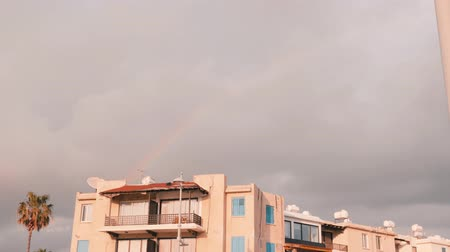 гром : Rainbow in the sky. Rainbow after rain. Appearance of rainbow after storm. Gray cloudy sky in bad weather. Colorful curve with building in the front Стоковые видеозаписи