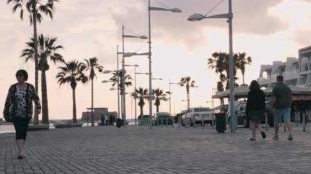 godo : March, 16, 2019  Cyprus, Paphos Beautiful quay with cars and pedestrian path. Tourists walking on promenade in Paphos, Cyprus. Tourist promenade with palms. Tourist zone with cafes and shops