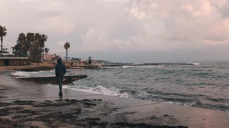 カモメ : Young lonely boy walking through deserted seacoast. Melancholy man walking along promenade. Young boy is sad. Bad stormy weather at city promenade. Sea promenade at storm.