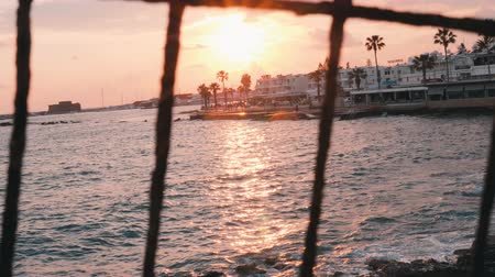 horizont : Sunset through lattice. Pink sunset through fence. Beautiful sea sunset. Pink sunset on marina. Tourist promenade on sunset. Pink sunset rays. Beautiful sunset rays. Sunset path.
