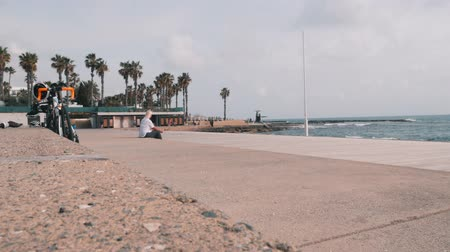 kypr : March, 16, 2019  Cyprus, Paphos. Beautiful tourist promenade with people walking along beach. Tourist zone with cafes and souvenir shops. Male runner training along pier. Beautiful pier with stormy sea