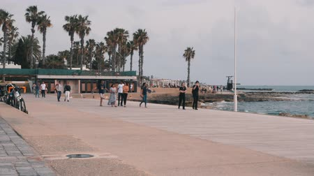 andar : March, 16, 2019  Cyprus, Paphos. Indonesian family walking at tourist promenade and enjoying vacation. Tourists strolling along beach of Mediterranean sea. Tourist zone with palms and beach area