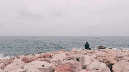 think big : Lonely sad man sitting on big stone near ocean. Office worker sitting near sea after work day. Isolated lonely boy looking at sea. Rocky seacoast with big waves. Mediterranean sea with big waves