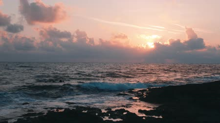 unutulmayan : Beautiful evening twilight on mediterranean sea. Evening sunset. Pink rays of setting sun. Stormy ocean on with pink sky and clouds on background. Sun sets behind clouds. Unforgettable sea sunset