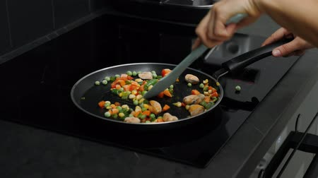 vegetable wok : Fried vegetables on induction pan on smart modern kitchen. Cookery process. Female hands preparing boiled vegetables on pan. Healthy food