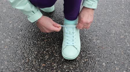 elderly care : Senior old Caucasian woman laces her shoes before running in the snowy winter park. Close up Front shot