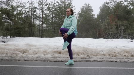 chica campo : Senior old Caucasian woman warms up stretching before running in the snowy winter park. Side shot. Slow motion