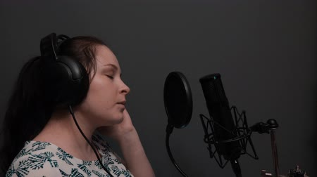 vokal : Close up side view of singing girl in headphones in recording studio. Vocal training. Romantic singing