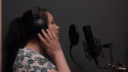 rehearsing : Romantic pop disco female singer starting to sing. Girl in headphones is rehearsing song in professional recording studio