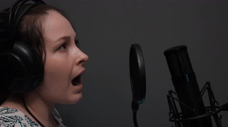 vokální : Close up side view of cute girl in headphones is singing song. Emotional dramatic singing. Professional vocal studio