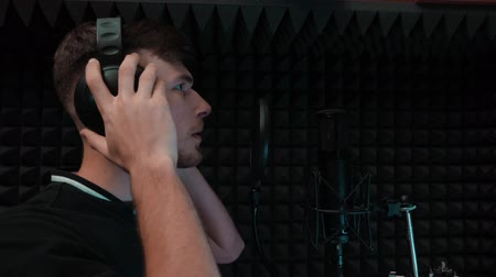 голос : Young handsome vocal artist singing song at home music studio with black background. Pop male singer recording voice. Professional vocal studio
