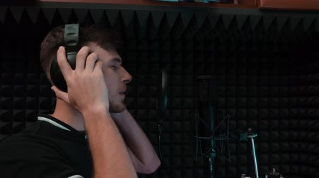 vokální : Close up of young romantic pop male singer in headphones. Vocal artist singing with closed eyes. Recording at home music studio