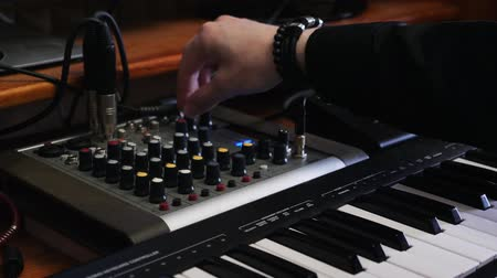 compresor : Music producer engineer turns knobs on mixing board with equalizer. Home studio recording mixing and mastering process. Electronic midi piano and mixing board. Home recording music studio.