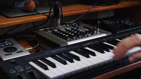 sztereó : Home music recording studio workspace with mixing board soundboard and keyboard. Sound engineer turning knobs on sound mixer. Music recording concept.