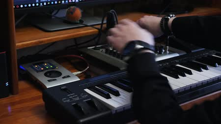 compresor : Sound engineer work station with soundboard midi piano and sound engineer mixing board. Hands turning knobs and pushing buttons with equalizer while creating and mixing pop rock music. Archivo de Video