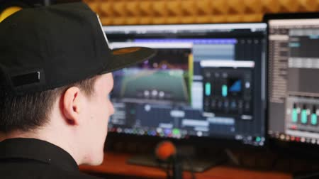 compresor : Young sound producer creating music at home studio. Sound engineer recording and mixing a song at home recording studio. Man looking at screen with sound equalizer and mixing board creating a song. Archivo de Video