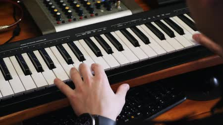 compresor : Home recording music studio. Hands playing on piano with mixing and mastering board and soundboard. Sound engineer composer writing pop rock song on piano at home studio. Archivo de Video