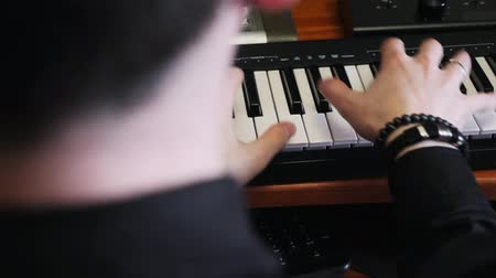 microphone : Hands playing on piano midi keyboard in music studio. Music composing process. Pop hit composer creating new song for music album. Home music recording studio concept.